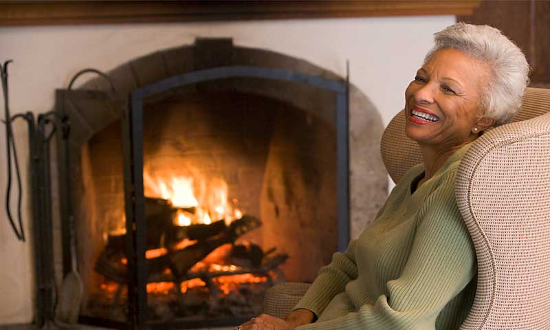 Woman relaxing by fireplace.
