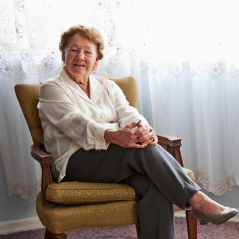 Retired woman sitting in chair.