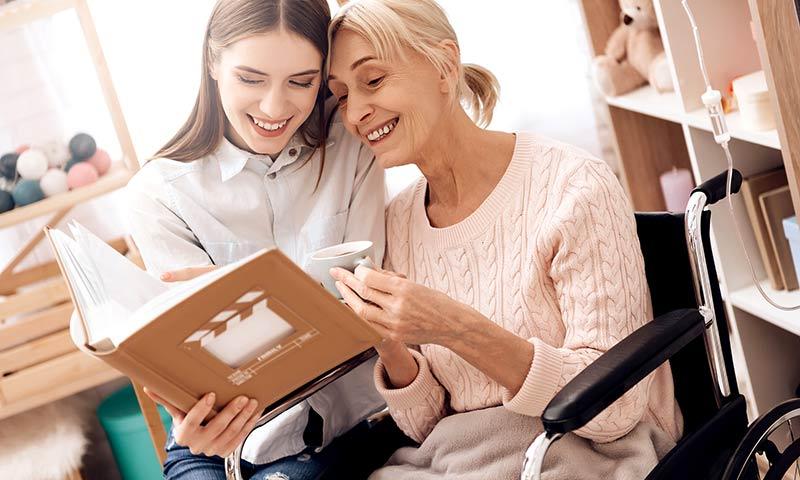 Women enjoying downsized scrapbook.