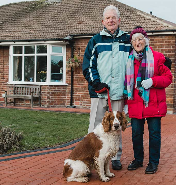 Couple and their dog standing by house.