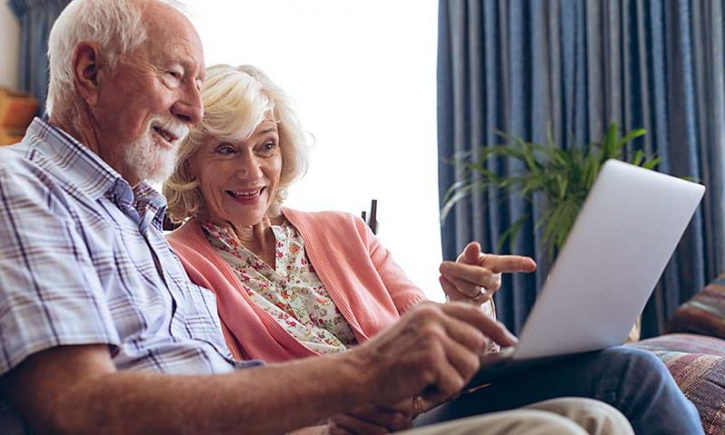 Couple looking at pictures on computer.